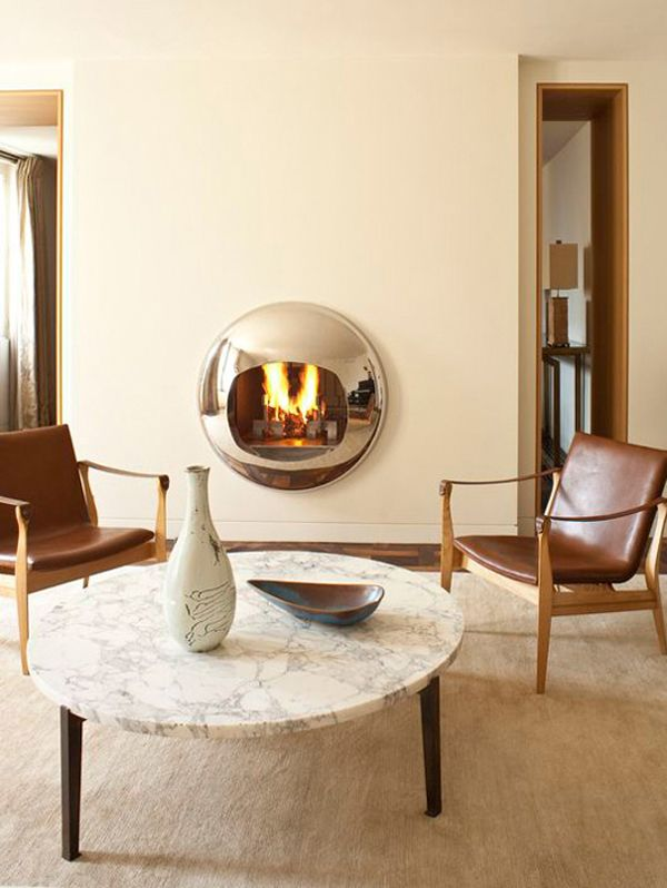 A polished bubble of a fireplace doubles as sculpture in this Paris apartment designed by Pierre Yovanovitch. Photo by Lux Productions.