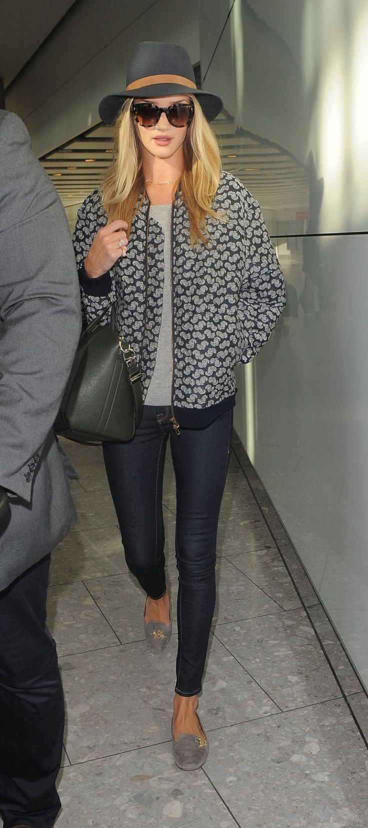 Rosie Huntington Whiteley looking gorgeous in a printed bomber, paired with simple, neutral accessories and dark shades.