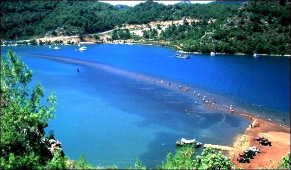 Kızkumu, Muğla, Turkiye.  Kızkumu is an area of 600 meter shallow water that divides this bay of Turkey into two and is part of Orhaniye District of the city Muğla in Turkiye. According to the legend, a girl who wants to reach her lover fills her skirt with sand and start moving ahead in the sea by filling the sea with her sand. But she was drowned when she ran out of sand. Just at the beginning point of the shallow water area, there is a sculpture of this girl.