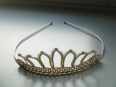 """I have attached the tatting to the headband using fine jewelry wire. The left one I added pearl beads at the same time. After I had assembled the tiaras I felt that they were not stiff enough - I had used """"Fraycheck"""" - and so I dipped the tatting in full strength PVA glue, wiped off the excess with a damp cloth and reshaped the tatting by moulding them against curmpled alluminium foil. The stiffness is now perfect!"""