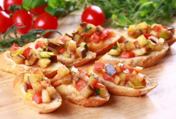 Felii de baghetă ratatouille -  E un festin al legumelor: roşii, vinete, ceapă, zucchini într-o combinaţie savuroasă servită pe felii crocante de baghetă.