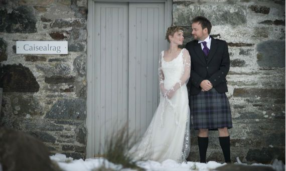 A wedding couple stand looking into each others eyes as they stand outside a cottage