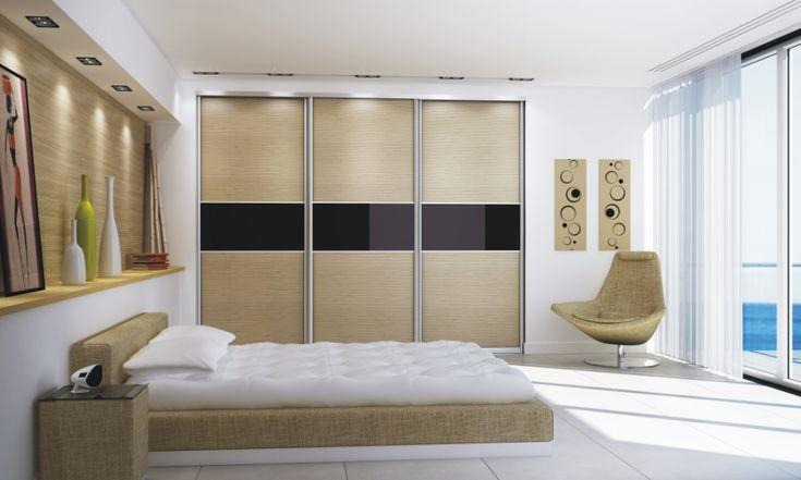 Spokojna elegancja. Szafa wnękowa z trzema skrzydłami drzwi przesuwnych.Wypełnienie drzwi: mata bambusowa oraz elegancji lacobel w kolorze burgundu. Całość podkreśla zamontowane oświetlenie halogenowe.