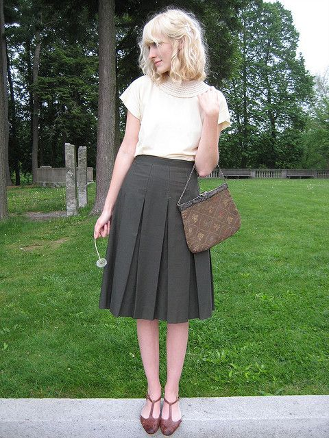 the snail and the cyclops. cream blouse with beautiful collar, black pleated midi skirt, strappy flats and a charming bag.