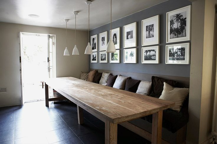 Long wooden table with bench seating and pillows behind it.