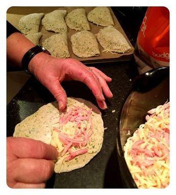 madkasse Pirogger (ca. 15 stk) Dej 2 dl kogende vand 125 g. frossen spinat (3 kugler) 1 1/2 dl mælk 50 g. gær 1 1/2 spsk olie 1 1/2 tsk salt 1 lille bakke karse 1 dl. friskklippet purløg 100 g. rugmel 50 g. hvedeklid 500-600 g. hvedemel Fyld 200 revet ost 200 finthakket eller revet skinke æg til pensling