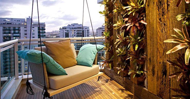 Cantinho confortável para a varanda com paredes decoradas por vasos com bromélias e dormentes e uma poltrona suspensa por cordas náuticas.
