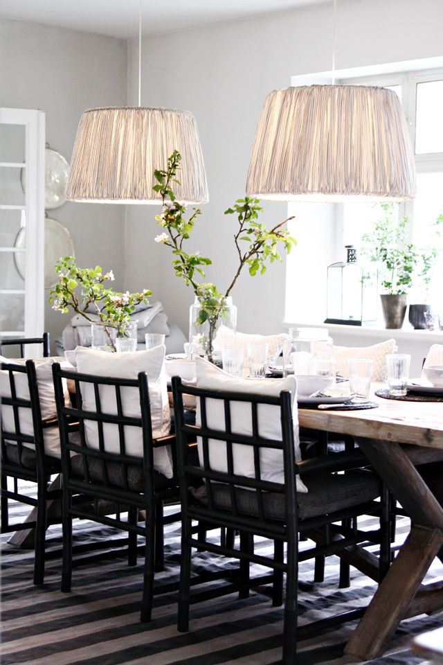Fantastic monochromatic dining space with weathered x base table, striped rug, a pair of pendants and black dining chairs,