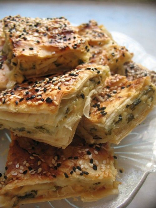 Börek (also burek and other variants) is a family of baked or fried filled pastries made of a thin flaky dough known as phyllo (or yufka). It can be filled with cheese, often feta, sirene or kaşar; minced meat, or vegetables. Most probably invented in what is now Modern Turkey, in the Anatolian Provinces of the Ottoman Empire in its early era, to become a popular element of Ottoman cuisine.[1][2][3] A börek may be prepared in a large pan and cut into portions after baking, or as individual…