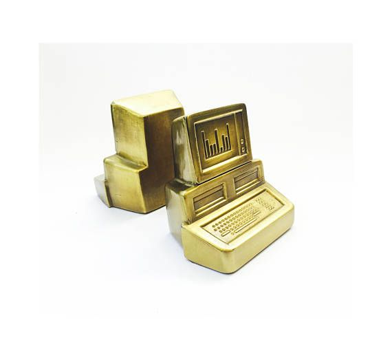 A pair of heavy vintage brass bookends in the shape of computers. Each bookend has a nice brushed finish to the brass and felted bottoms. Marked by the manufacturer on the base Pm Craftsman.  In excellent condition showing very minor age appropriate wear. No major scratches or dents.  Each measures 5 wide x 4 deep x 5 tall.
