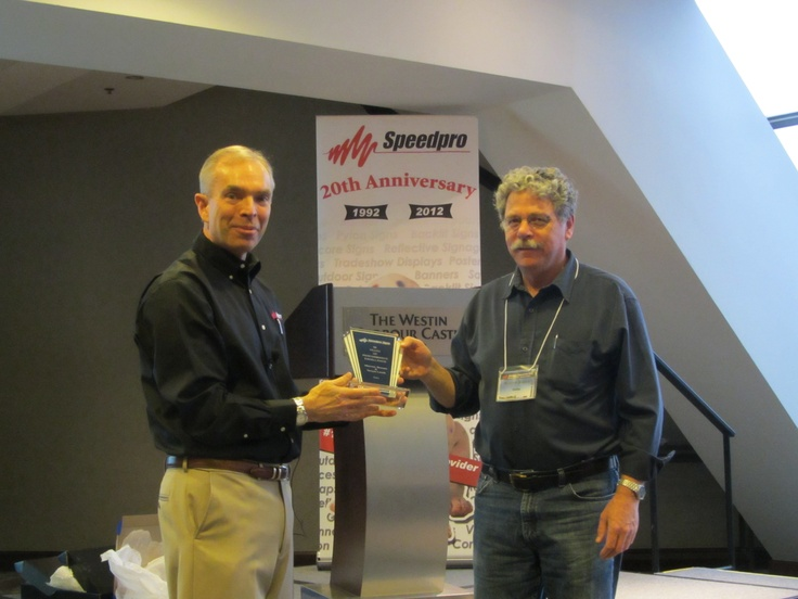 Warren of Speedpro Signs Delta BC accepts his 10th Anniversary award from Speedpro President, Stuart Burns.