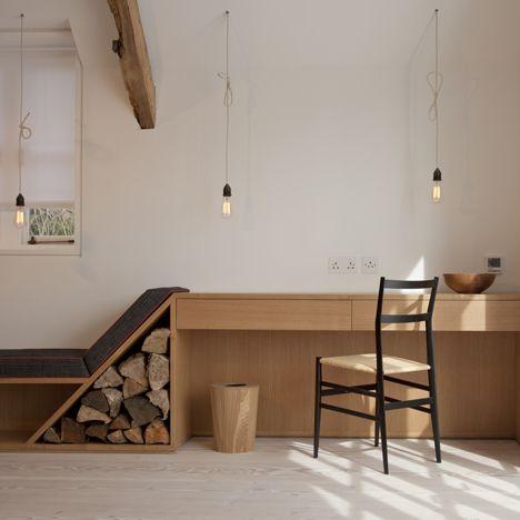 Mooi side meubel van bureau en bank, ook leuk voorbeeld van over hele muur van woonkamer waar onder bank ook gedeeltelijk opbergruimte is gemaakt.
