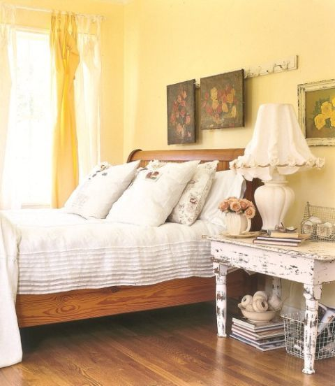 Pale yellow walls set a soothing tone in this cozy Texas guest bedroom. The hooks on a vintage French coatrack that once hung in a train now display paintings and the bed is topped with a sheer bedcover with a pin-tucked hem.