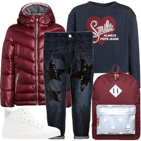 Jeans baggy blu scuro con applicazioni di stelle in paillettes abbinati a maglietta a manica lunga blu navy con stampa e piumino rosso con cappuccio. Completano l'outfit le sneakers alte color bianco e argento e lo zainetto rosso e grigio.