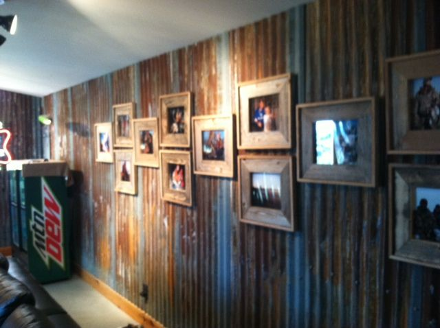 Old barnwood picture frames on a rusted tin wall from a barn roof found at the - Rustic wall covering ideas ...