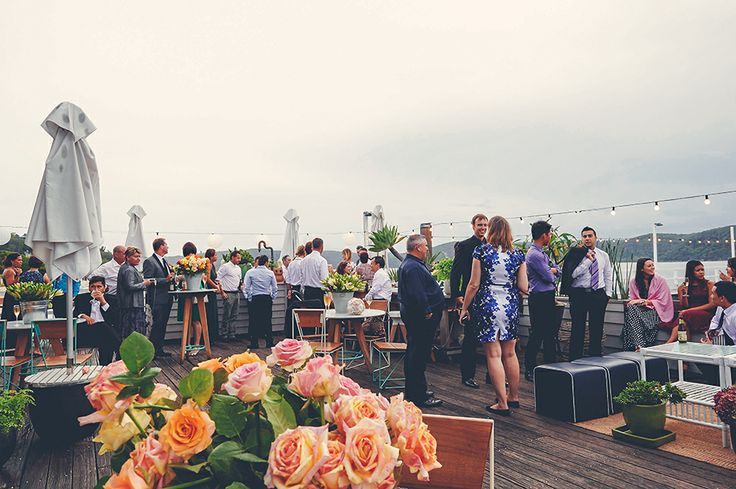 Wedding guests enjoying canapés under the open sky at The Boathouse, Palm Beach   Photo Credit: Popcorn Photography