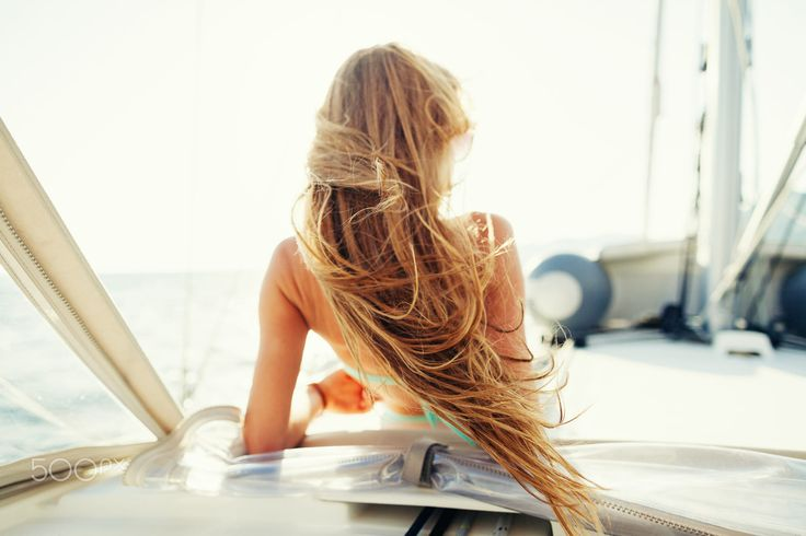 wind in hair yachting girl yachting on sailboat. Back view