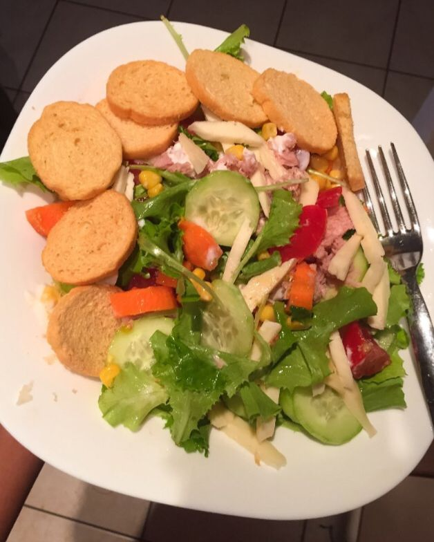 Healthy salad with some round sliced of baked bread to accompany with.  1- Italian made cheese 2- fresh carrots 3- canned meat 4- cucumber  5- sweet tomatoes 6- sweet canned corn 7- olive oil(