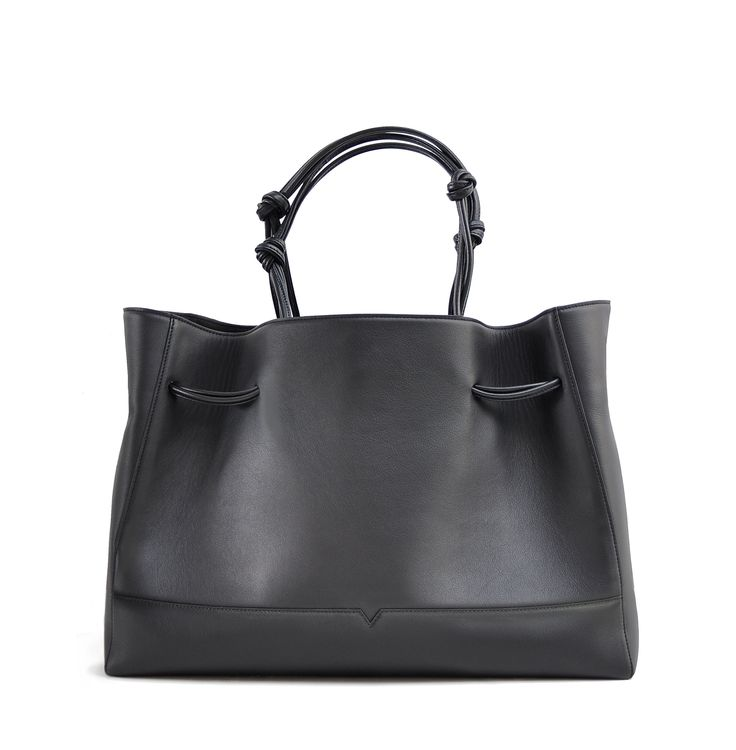 The Tote in Black from von Holzhausen made from natural grained soft Italian leather with painted edges. Shoulder straps elongate when worn for a comfortable fit. Features two open pockets on interior and removable signature wallet.