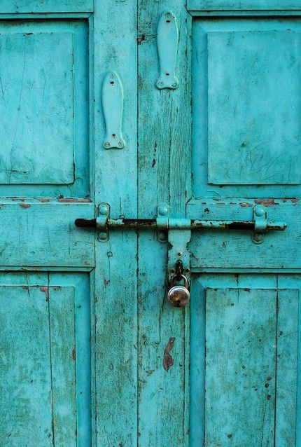 Turquoise door with little fishy escutcheons.