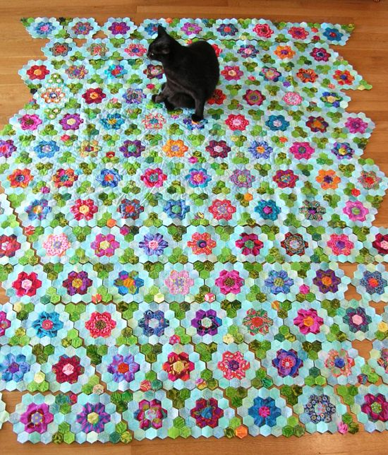 That's exactly what my cat does when my quilts are laid out. (Except he sprawls.)