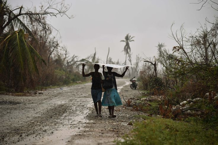 Les Cayes, Haiti  Women walk, protecting themselves from the rain, in the commune of Chadonyer, Haiti. The UN secretary general, Ban Ki-moon, visited victims of hurricane Matthew last week, saying the destruction was 'heartbreaking'. He renewed a pledge to help the nation cope with an outbreak of cholera that was introduced by UN peacekeepers after Haiti's devastating earthquake in 2010.