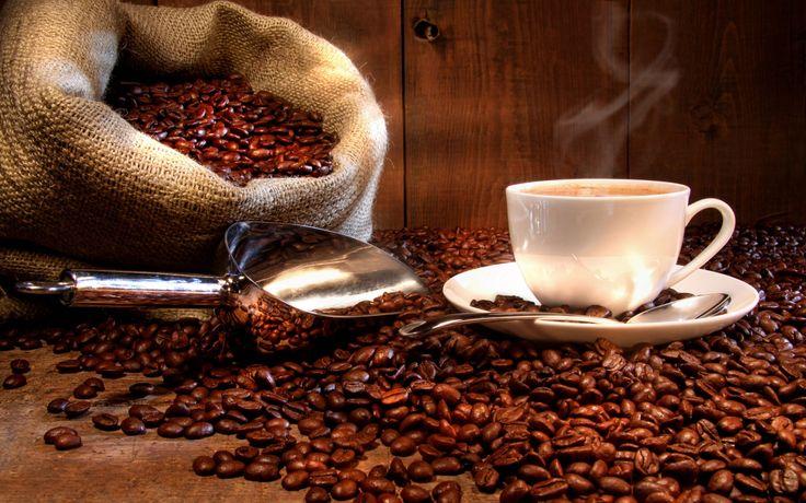 Taza de cafe humeante junto a un saco de arpillera lleno de granos de cafe natural tostado. Fotografia by Sandra Cunningham y depositada en Dreamstime.