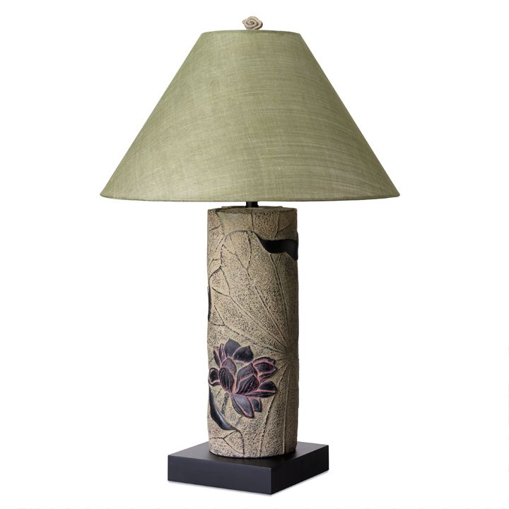 The base of this lovely lamp includes a beautiful decoration of a lotus flower - symbol of purity and long life. It comes with a silk shade as shown.