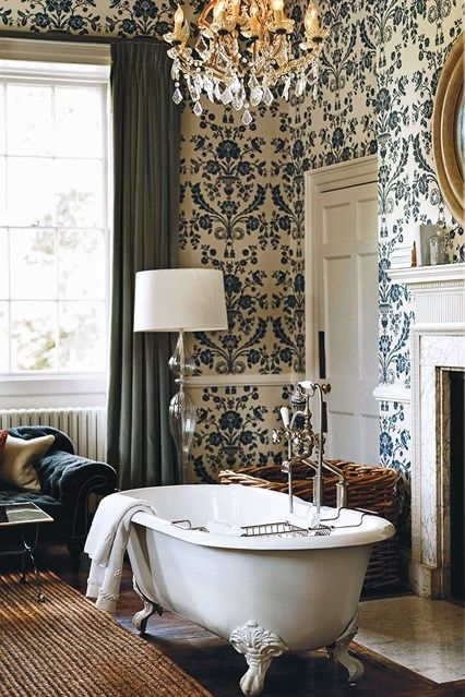 Clawfoot tub, floral wallpaper and antique chandeliers in a blue and white bathroom at Babington House hotel in Somerset, England | Best hotels for family holidays in Britain | UK breaks (Condé Nast Traveller)