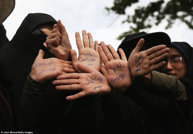 Women hold up their hands pledging to offer their lives, if needed, for the Islamic Revolu...