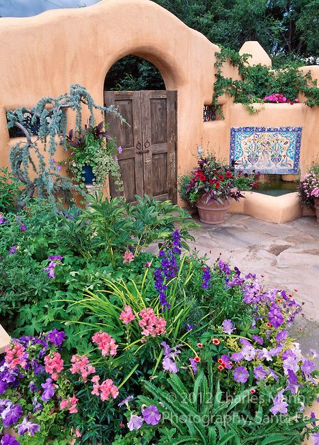 Susan Blevins of Taos, New Mexico, created an elaborate home garden featuring containers, perennial beds, a Japanese themed path and a regional style that reflects the Spanish and pueblo architecture of the area. A stucco gate is embellished with a mosaic and bright container plantings.