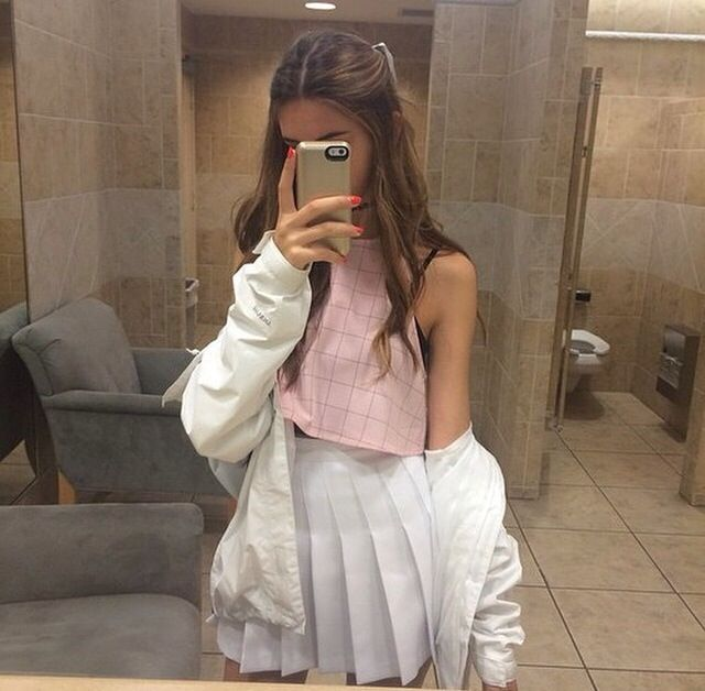 Pink cropped top, white pleated skirt and white jacket