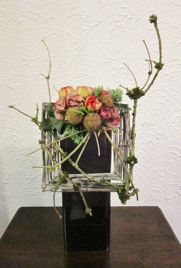 Flower arrangement with list of branches on vase  ~ source unknown