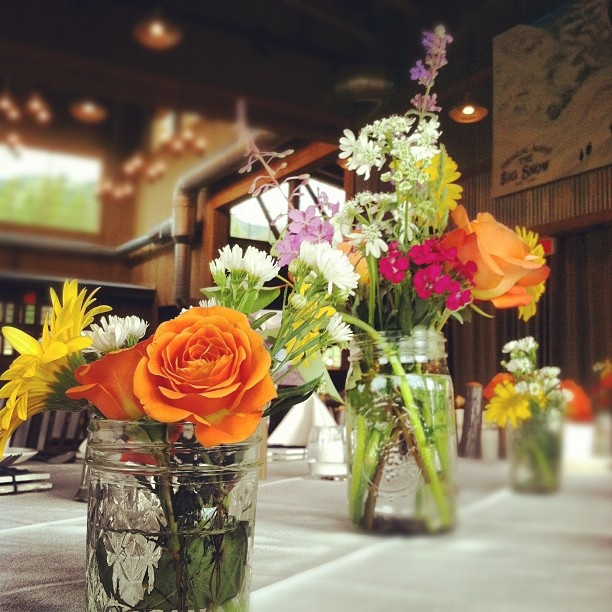 Wildflower-themed centerpieces using mismatched vintage glass and mason jars.  Ten Mile Station, Breckenridge, Colorado.