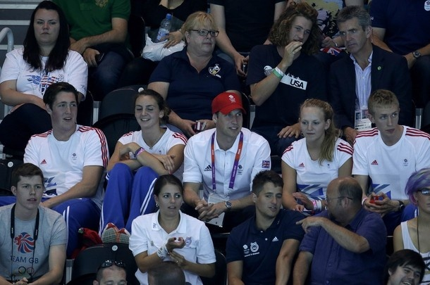 Britain's Prince William, center in red hat, watches the Britain men's water polo team play against Serbia during a preliminary match at the 2012 Summer Olympics, Tuesday, July 31, 2012, in London.
