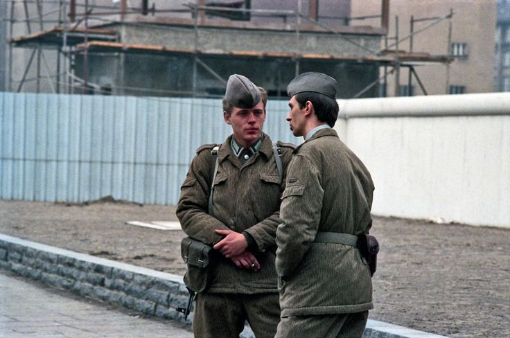 Two DDR Grenzpolizei standing on the western side of the border controls on Friedrichstrasse at Checkpoint Charlie, though still on DDR territory. This rarely happened, because they were not be trusted to go just a step away from the border. (1985) Photographed by Chris John Dewitt