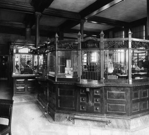 "Interior view of the First National Bank, Colorado Springs, El Paso County, Colorado, features coffered wood ceilings and an ornate, three-windowed tellers box and brass footrails under writing shelves. A. H. Hunt, the cashier is behind beaded grating and another man stands in the background. Signs read: ""Cashier"" ""Teller"" ""Next Window"" and ""Revenue Stamps for sale at this window."" Date	[between 1910 and 1920?]"