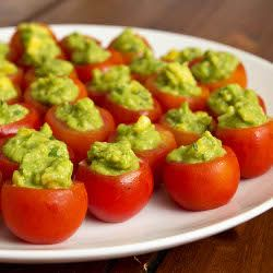 Cherry tomatoes stuffed with guacamole, an appetizer in one perfect bite.
