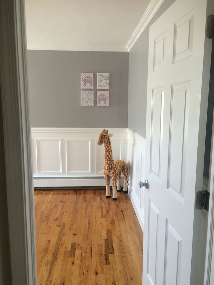 Nursery entry way. Grey walls, wainscotting, giraffe