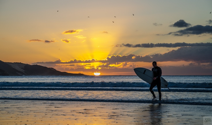 Surfing at Ahipara Beach, New Zealand, as the sun sets over the horizon. Glorious.