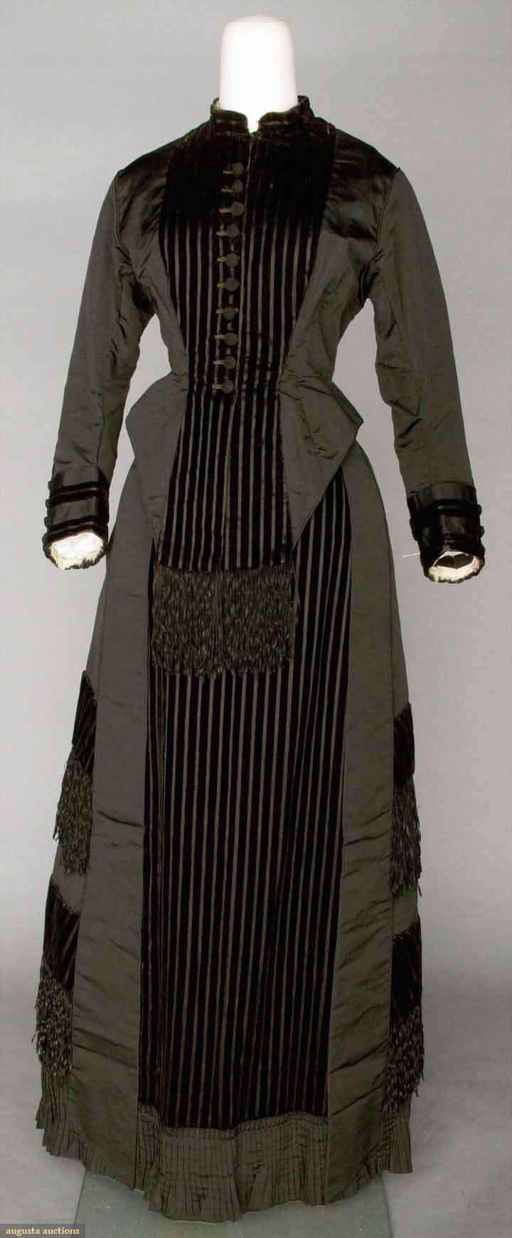 BLACK SILK DINNER DRESS, 1878 2-piece silk faille, skirt & bodice w/ panels of woven velvet stripes & crimped silk fringe, bodice w/ long back peplum trimmed w/ bows, white tulle sleeve & neck ruffles.
