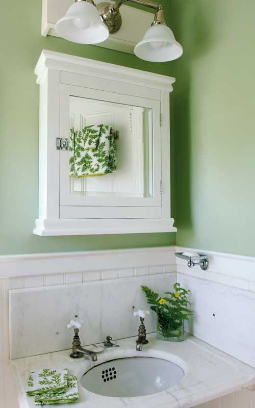 In a seaside cottage in Maine, walls painted in Farrow & Ball 'Green Ground' complement the original, tiny marble corner sink and cabinet. Photo by Edward Addeo.