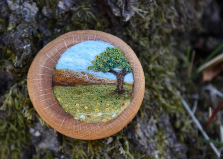 Artist Lisa Jordan creates these tiny brooches by needle felting wool, and then attaching them to found pieces of oak