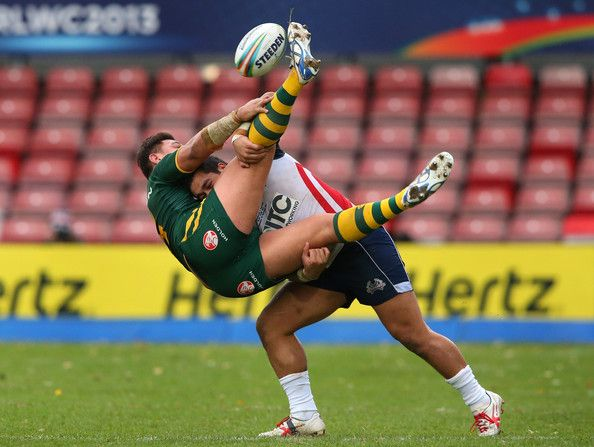 Josh Papalii Photos - Josh Papalii of Australia is tackled by Bureta Faraimo of USA during the Rugby League World Cup Quarter Final match between Australia and USA at Racecourse Ground on November 16, 2013 in Wrexham, Wales. - Australia v USA - Rugby League World Cup Quarter Final