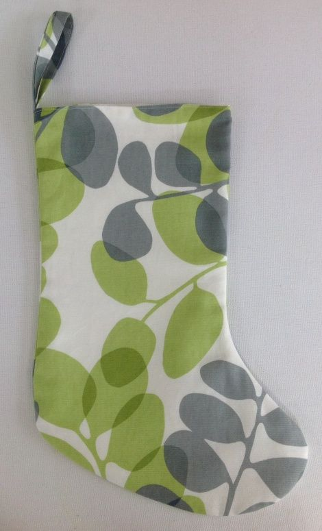 A summer Christmas stocking in a striking botanical print, echoing the abundance of summer plants. Made in Wellington, NZ from a lime green, grey and ivory cotton and fully lined with ivory cotton duck cloth.  Dimensions - width (when flat): 20.5cm; length (top to heel): 31cm; length (heel to toe): 27cm; hanging loop: 18mm x 12cm drop.