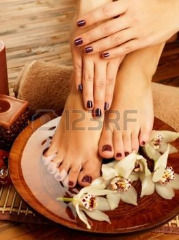 spa: Closeup photo of a female feet at spa salon on pedicure procedure. Female legs in water decoration  the flowers.