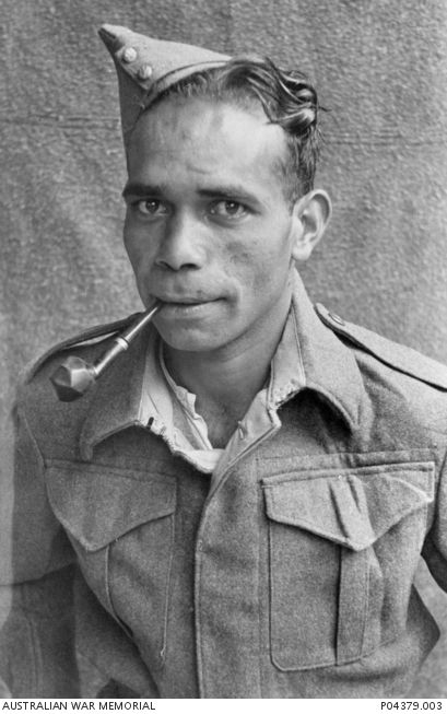 Portrait of Tommy Negus Green, Prisoner of War at Stalag XIIIc at Hammelburg, smoking a pipe. Green, an aboriginal serviceman, had been named 'Negus' by the German guards at the camp. He is probably NX22784 Thomas Harold Green, 2/1 Battalion of Collarenebri, NSW (born at Booyulgil [Baryulgil]).