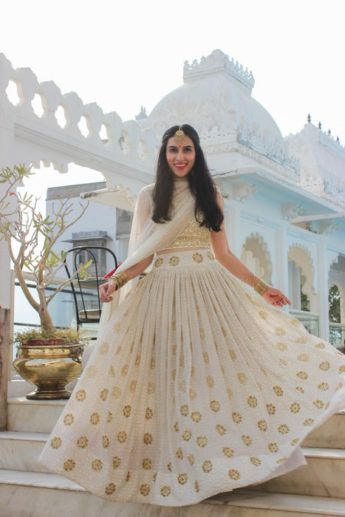 Light Lehengas - White and Gold Light Lehenga | WedMeGood | White Lehenga with Small Gold Booties, White and Gold Choli and Gold Jewelry #wedmegood #indianwedding #indianbride #lehenga #lightlehenga #white #whiteoutfit #twirling