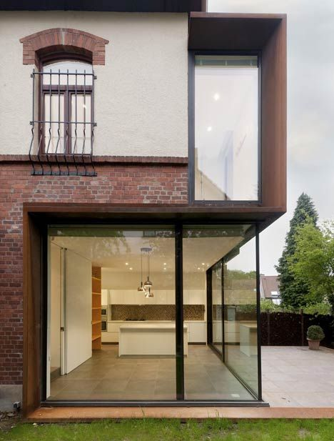 """Rethinking of the boundaries of a house. Belgian studio EXAR Architecture have replaced walls of brick and plaster with glass and Corten steel on this extension to a suburban house outside Brussels. The """"back"""" rooms, kitchen, bathroom, previously considered as services, blocked the views from the house to the nice garden."""