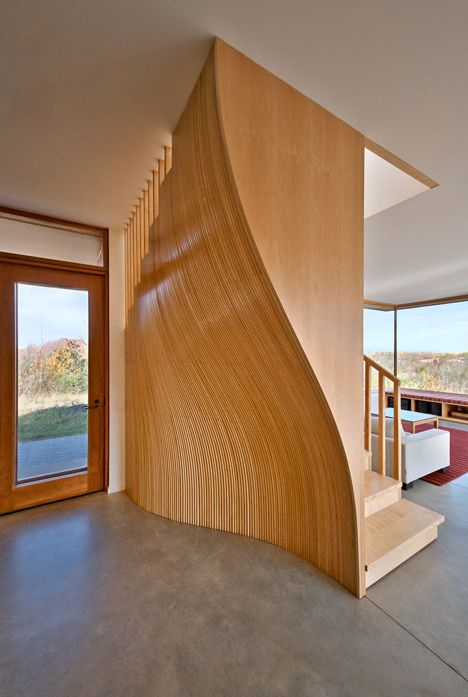 staircase is screened behind an undulating timber wall